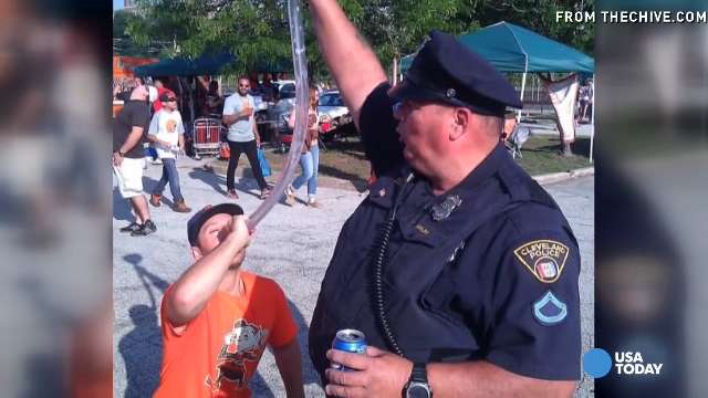 Cleveland cop appears to hold 'beer bong' for tailgater
