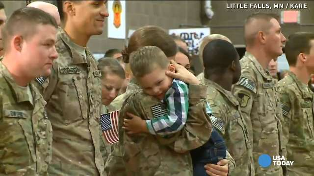 Toddler runs into mom's arms in Little Falls, Minn., despite military protocols.
