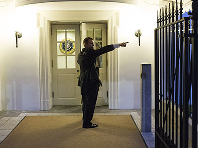 A Secret Service police officer holds a weapon as he stands near an entrance to the White House complex during an evacuation.