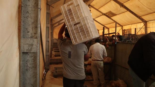 A man hauls bags of yellow split peas, part of a U.S. food aid shipment to Burkina Faso.