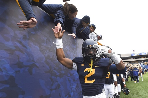 West Virginia's Shaquille Riddick and K.J. Dillon celebrate their Baylor win with fans Saturday.