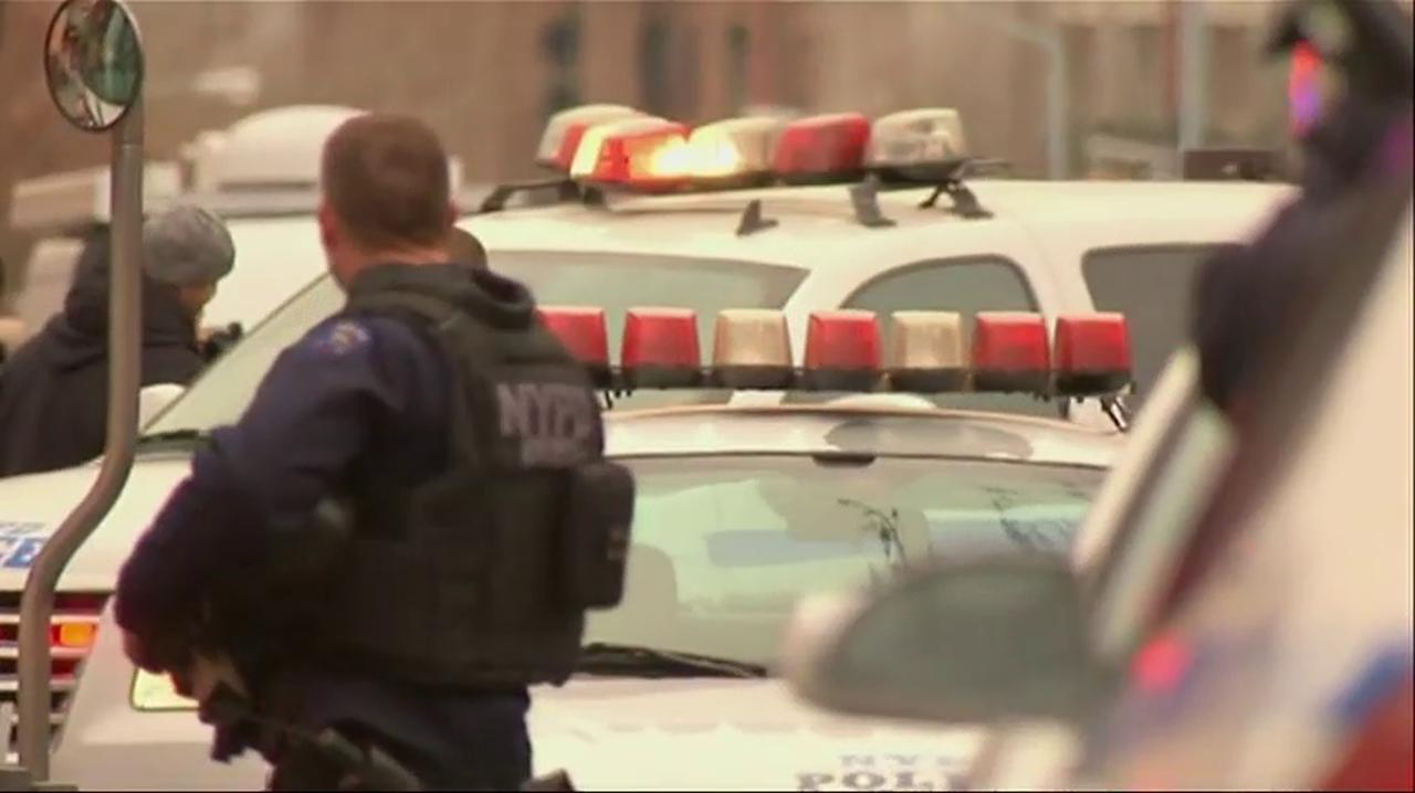 Investigators work in the area where two NYPD officers