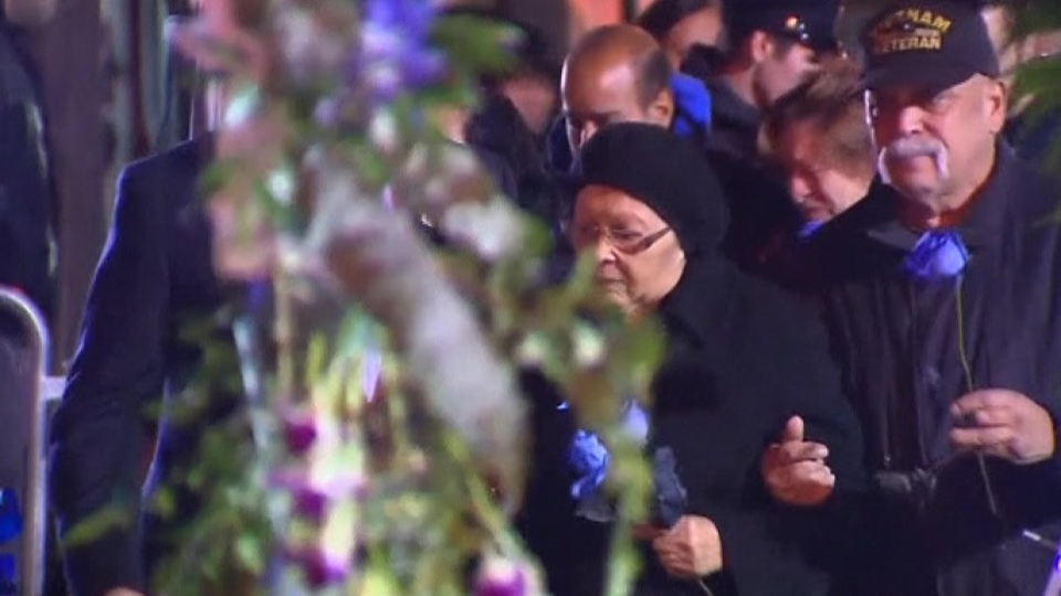 Rows of blue roses at vigil for slain NYPD officers
