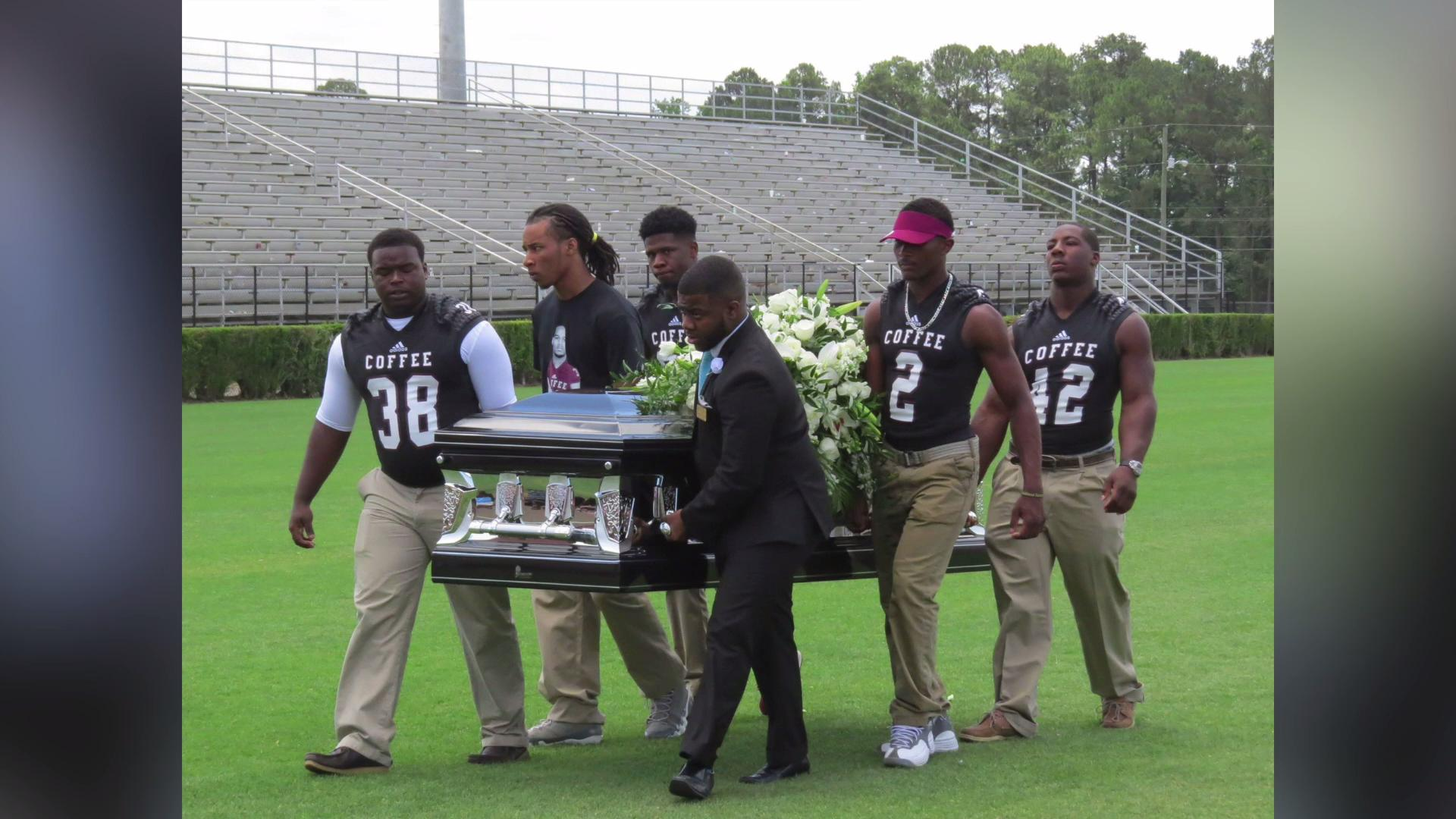 Football players carry teammate's coffin into the end zone