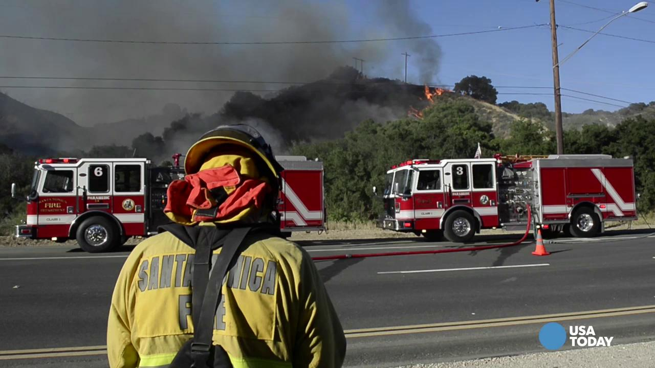 Firefighters work a ridge off of The Old Road in the