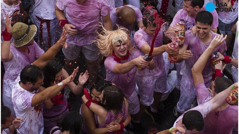 Revelers open their mouths as they wait to cool off with water thrown from a balcony to celebrate the official opening of the 2015 San Fermin Fiestas, in Pamplona, northern Spain, Monday, July 6, 2015.