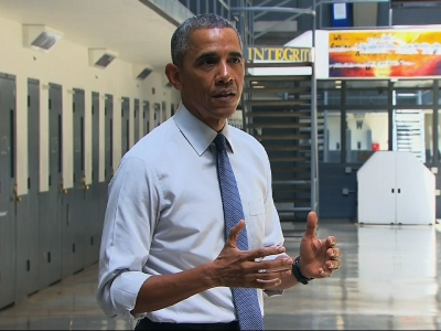 President Obama, alongside Charles Samuels (R), Bureau of Prisons Director, and Ronald Warlick (L), a correctional officer, tours a cell block at the El Reno Federal Correctional Institution in El Reno, Oklahoma.