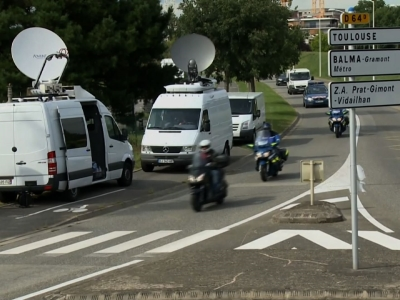 A white van, accompanied by police motorcycles and