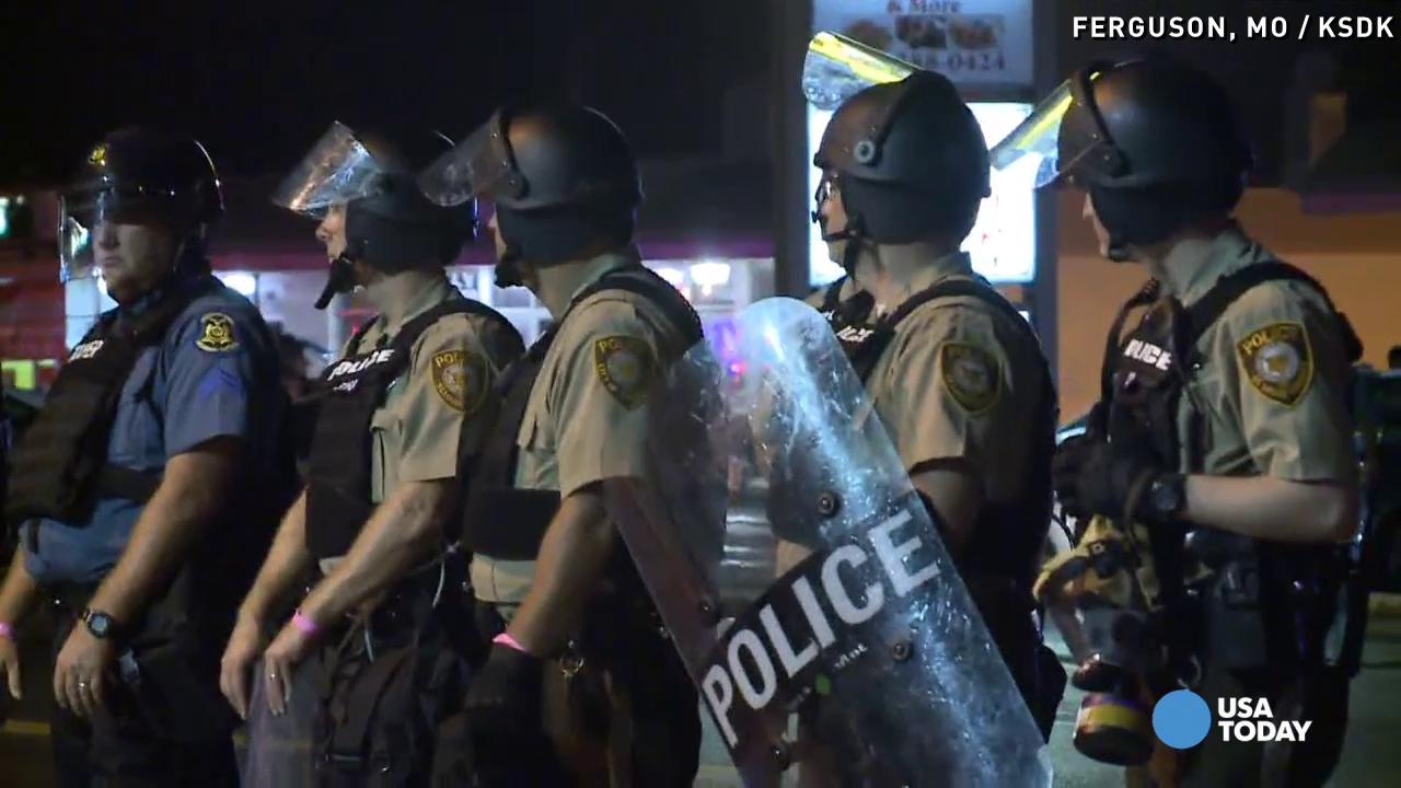 Members of the St. Louis County police force stand  ready to respond in Ferguson, Mo.