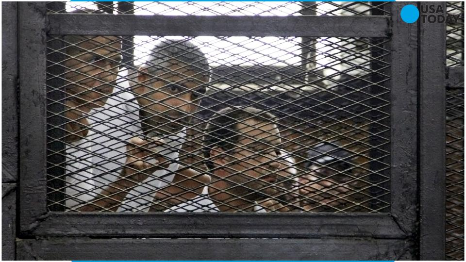 Canadian Al-Jazeera English journalist Mohammed Fahmy, left, and his Egyptian colleague Baher Mohammed listen in a courtroom in Tora prison in Cairo, Egypt.