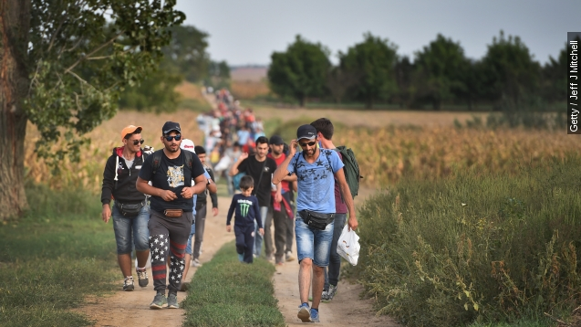 Two refugees head toward the Croatian village of Tovarnik, close to the official Serbia-Croatia border on Sept. 16, 2015.