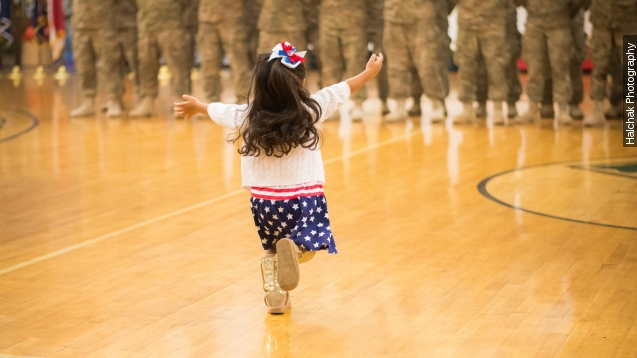 Little girl hugs dad before military ceremony ends