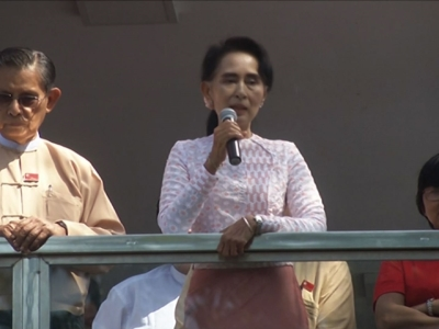 Leader of Burma's National League for Democracy party, Aung San Suu Kyi, right, delivers a speech with party patron Tin Oo from a balcony of her party's headquarters in Rangoon, Burma,  on Nov. 9, 2015.