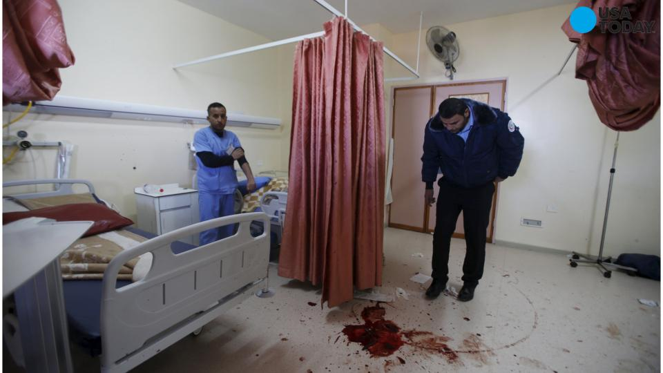 A Palestinian doctor shows a bullet hole at al-Ahli hospital in the West Bank town of Hebron after a man was shot dead during a raid by Israeli undercover agents on November 12, 2015.