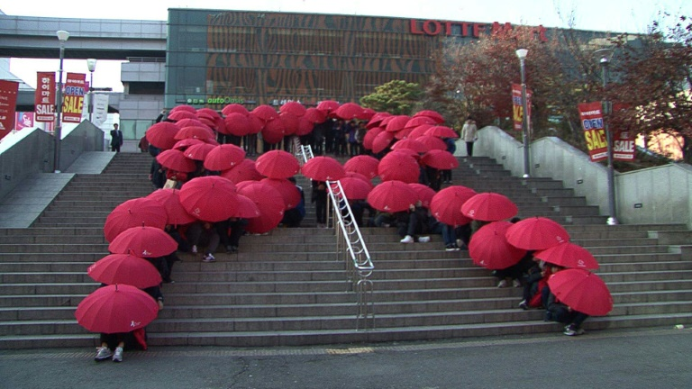 School boys make a human red ribbon with umbrellas to mark World AIDS Day in Seoul.