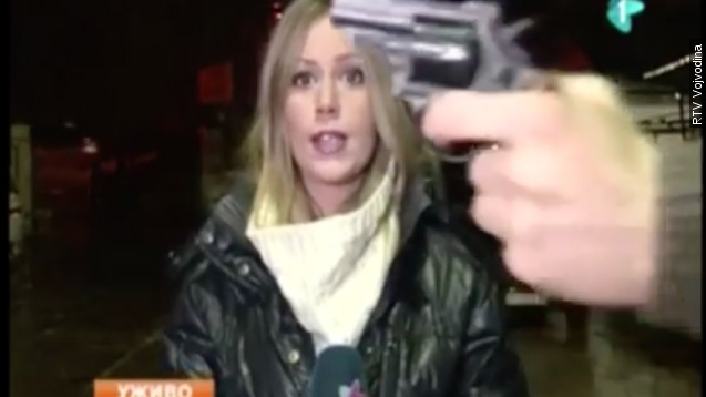 A man waved what appeared to be a gun in front of a Serbian reporter's face during a live television broadcast.