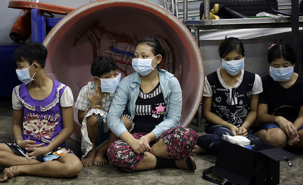 In this Nov. 9, 2015 photo, an undocumented child worker with children and teenagers to be registered by officials during a raid on a shrimp shed in Samut Sakhon, Thailand.
