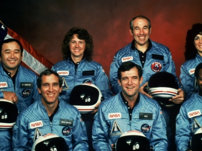 """Space Shuttle Challenger crew meets the media at the launch pad. Gregory Jarvis, Ellison Onizuka, Ron McNair, Christa McAuliffe, Judy Resnik, Michael Smith and Francis """"Dick"""" Scobee stand by the van."""