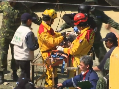 A rescue worker brings down a victim from the collapsed