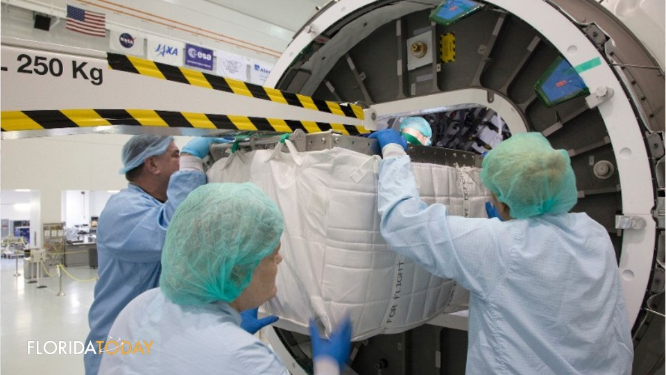Inside the Space Station Processing Facility high bay at Kennedy Space Center on Jan. 27, technicians prepare to load equipment and supplies into the Orbital ATK Cygnus pressurized cargo module using a customized insertion tool.