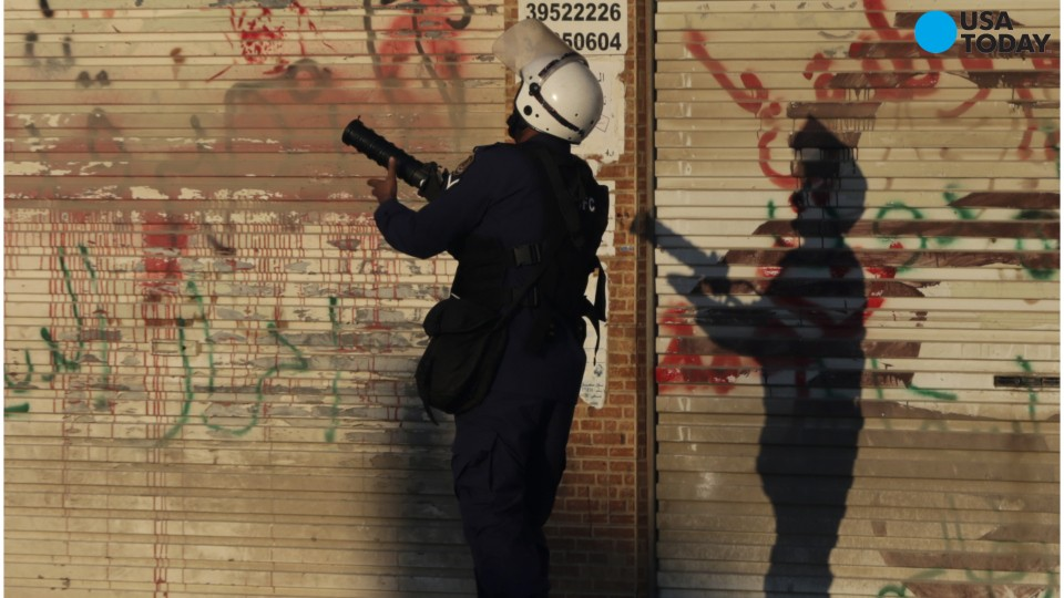 A Bahraini anti-government protester kicks away a tear gas canister fired by riot police in Sitra, Bahrain, on Sunday, Feb. 14, 2016.
