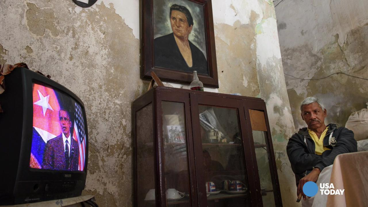 Sitting under a portrait of his grandmother, Angel Cuza watches President Obama's speech to the Cuban people inside his home in Old Havana on March 22, 2016.