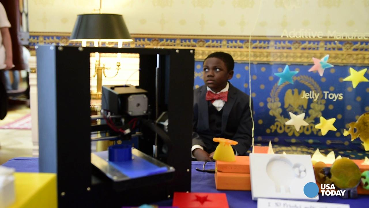 President Obama blows a bubble from a bubble wand made with a 3D printer by 9-year old Jacob Leggette while touring exhibits at the White House Science Fair.