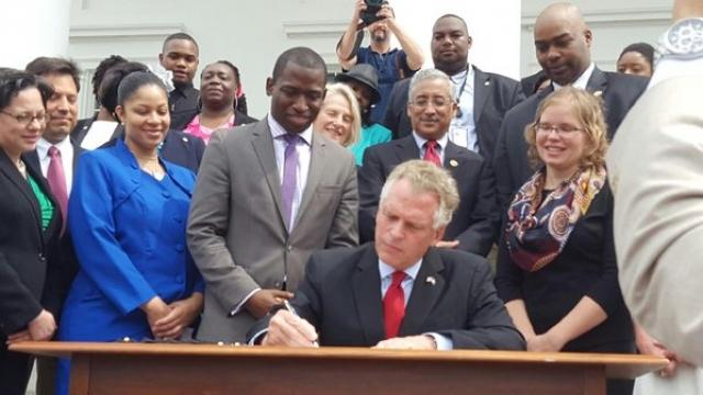 Gov. Terry McAuliffe holds up the order he signed to restore rights to felons in Virginia at the Capitol in Richmond, Va., on April 22, 2016.
