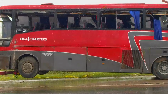 A damaged OGA Charters bus is hauled away after a fatal rollover on Saturday, May 14, 2016, south of the Dimmit-Webb County line on U.S. 83 North in Texas.
