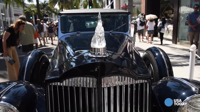 USA TODAY's Chris Woodyard chats with the owner of a customized 1937 Packard town car featuring a unique hood ornament at the Rodeo Drive Concours d'Elegance.