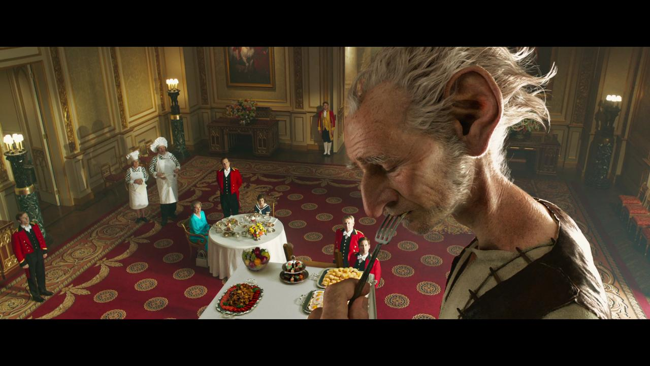 The BFG (aka the Big Friendly Giant, played by Mark Rylance) enjoys a meal with the Queen (Penelope Wilton) and his friend Sophie (Ruby Barnhill).