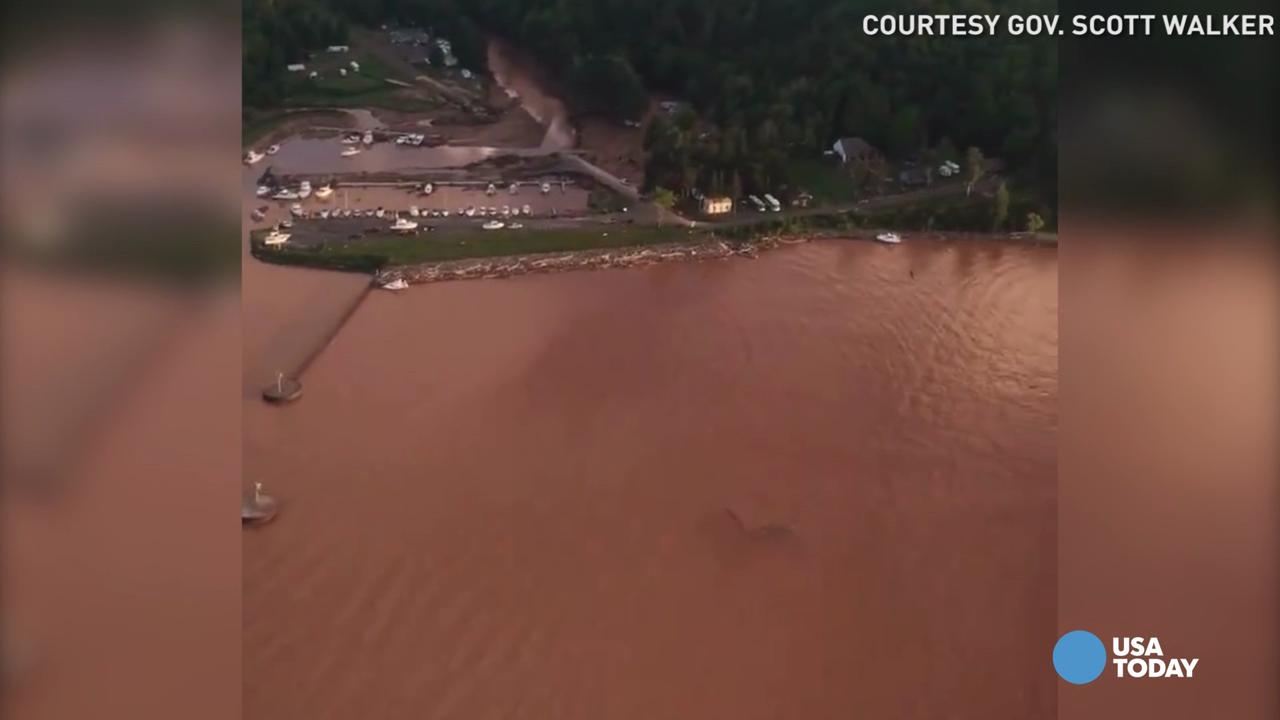 People observe part of Wisconsin Highway 13, washed out after heavy rains, south of Highbridge in Ashland on Tuesday, July 12, 2016. Storms carrying tornadoes, torrential rain and powerful winds damaged homes, deposited a snowplow in a tree and flooded highways in north-central Minnesota and northern Wisconsin.