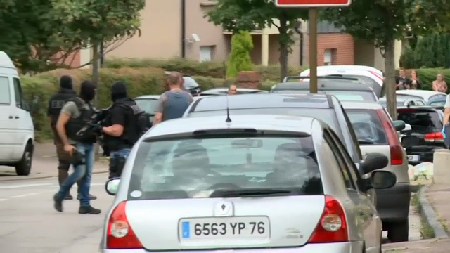 Police on Tuesday led away a man from a house in a neighborhood close to where an attack on a church left its 85-year-old priest dead. The Islamic State group has claimed responsibility for the attack. (July 26)