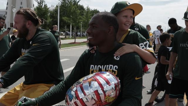 A young Packers fan lets Green Bay safety Ha Ha Clinton-Dix ride his bike back to Lambaeu Field after the second practice of the 2016 training camp.