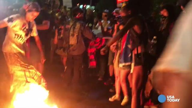 A protester at the Democratic National Convention caught fire while trying to stomp on a burning flag Wednesday evening.