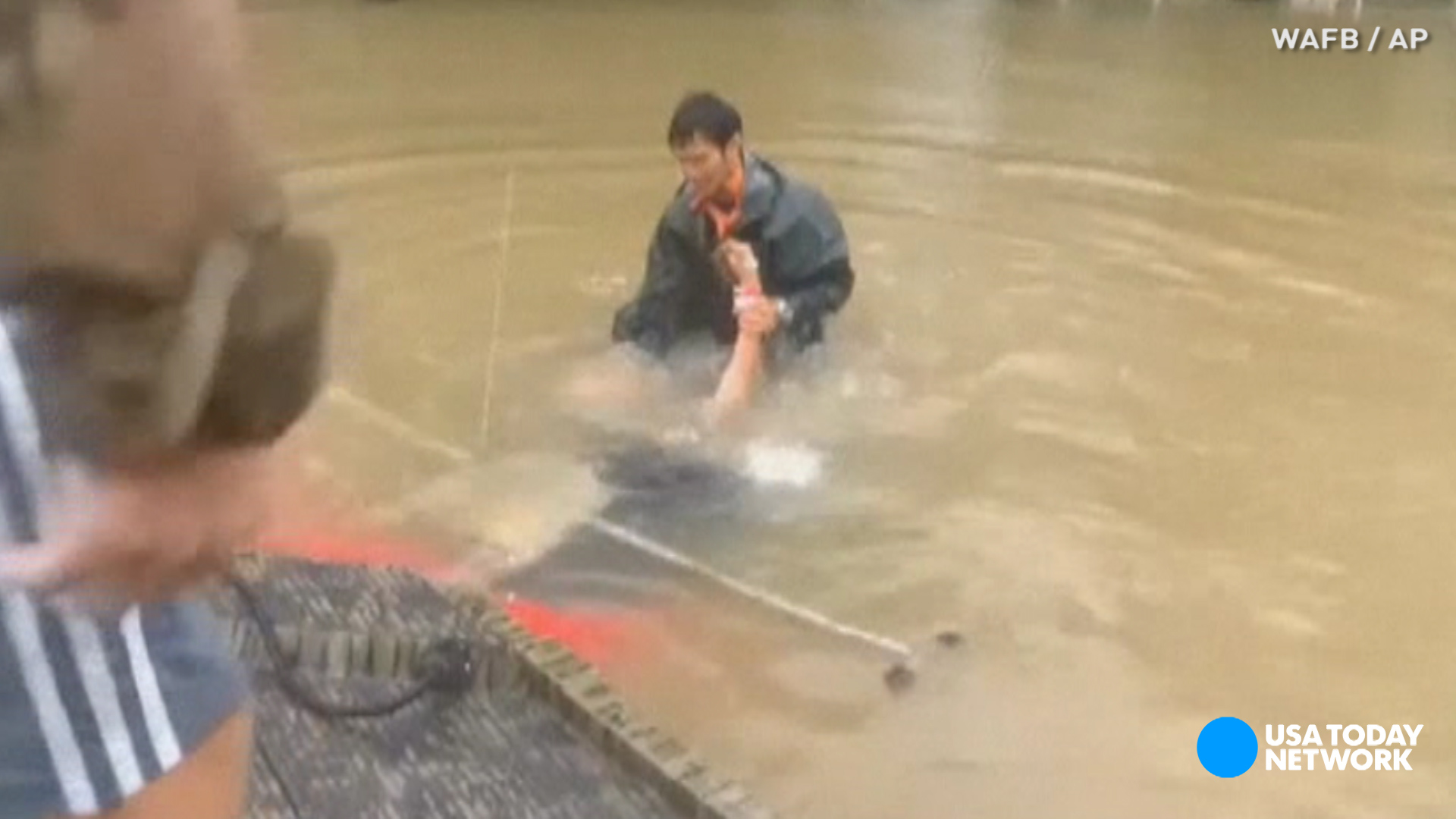 See rescue of woman and dog from car sinking in flood