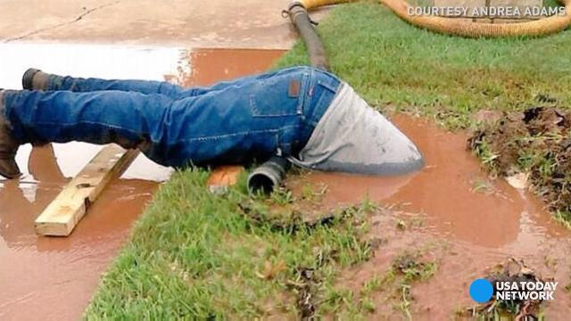 Jimmie Cox didn't think twice about plunging into a muddy puddle to fix a broken water line in Andrea Adams' yard. They never imagined how a far a photo of it would go.
