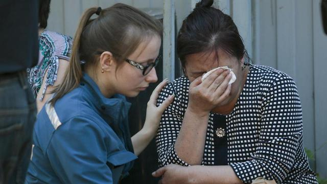 A rescued woman reacts at the site of a fire in a Moscow