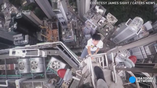 Sporting a helmet camera and accompanied by a drone, two teens climbed a Hong Kong skyscraper's tower spire.