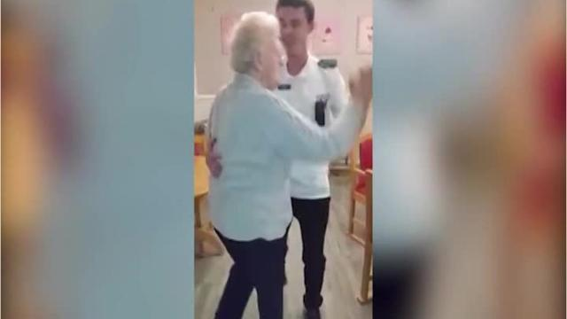 Elderly woman cheered up by dancing aide