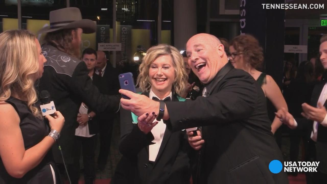 One reporter from The Tennessean was more than happy to take a selfie with Olivia Newton-John on the red carpet of the 50th Country Music Awards. His reaction was priceless.