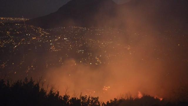 Firefighters work to extinguish a fire on Signal Hill in Cape Town, one of many fires that have destroyed homes, farms and other buildings in the western province of the South African city over the past two weeks.  Video provided by AFP