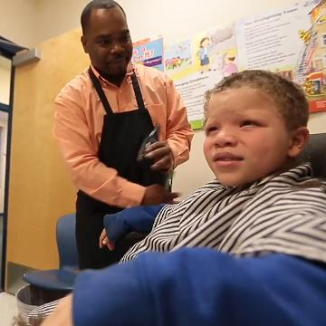 Barber gives kids free haircuts, with some class