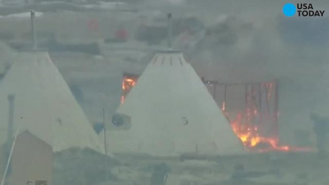 Dakota Access pipeline protesters set some of their tents and teepees ablaze Wednesday as the deadline loomed to depart their encampment near the Standing Rock Sioux reservation, in what might be seen as a final show of defiance.