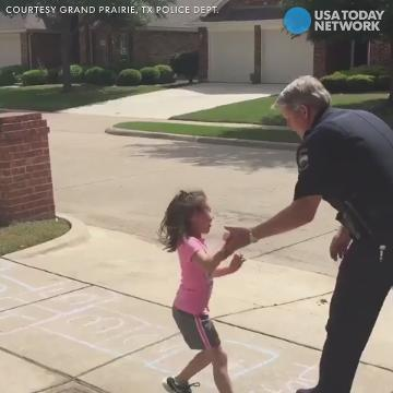 Cop plays hopscotch with little girl