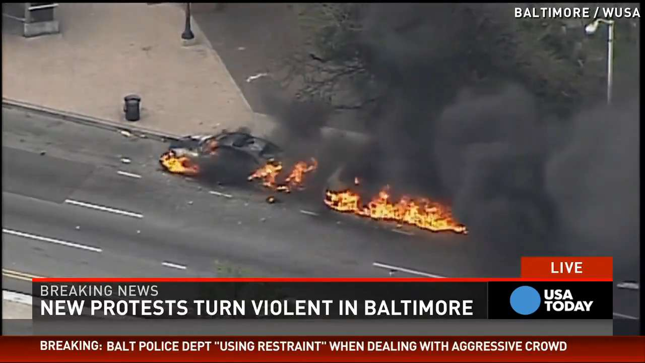 Protesters loot, set police car on fire in Baltimore