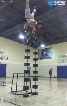 """The only thing more amazing than this man attempting a world record for the highest """"handstand tower""""  on stacks of dumbbells is the older gentleman sinking basket after basket behind him."""