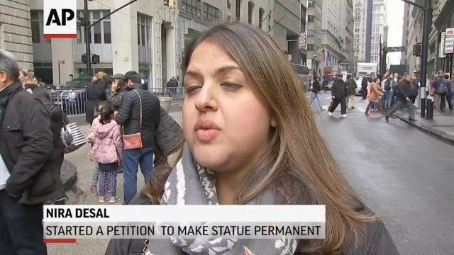 New York City has decided that the globally popular statue of a young girl staring down Wall Street's famous 'Charging Bull' will remain in place through February 2018. (March 27)