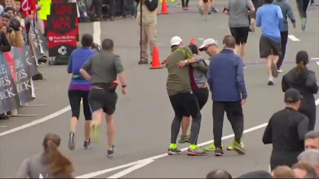 Raw: Exhausted runner carried to finish line