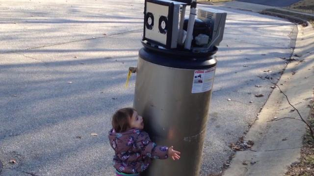 Little girl mistakes water heater as robot, gives it a big hug.